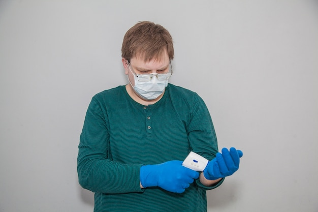 Man in masker en handschoenen met een thermometer tegen coronavirus