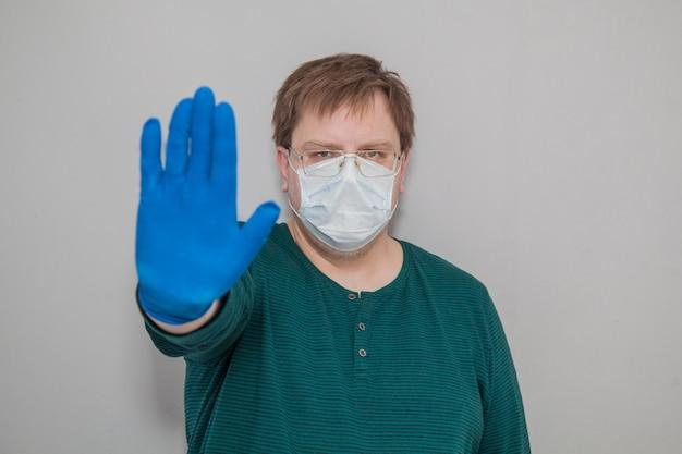 Man in masker en handschoenen toont einde