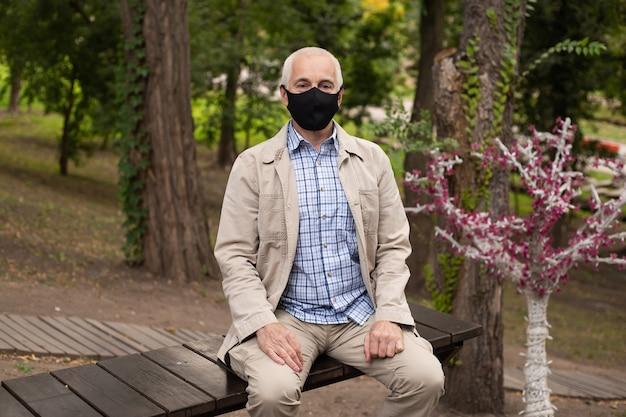 Man in masker in het park op de bank. bescherming tegen de ziekte. gezondheid veiligheidsconcept