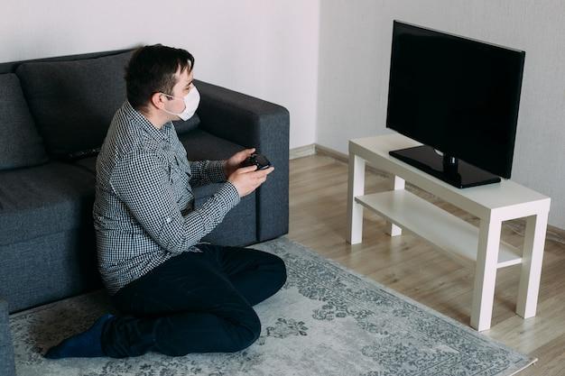 Man in masker spelen met spelcomputer op tv