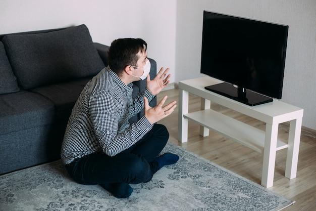 Man in masker tv-nieuws kijken