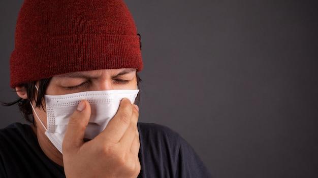 Man in medisch wegwerpmasker niest vanwege de flits 2019-ncov. coronavirus griep quarantaine close-up kopie ruimte.