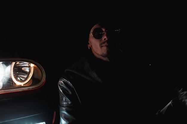 Man in modieuze kleding met zonnebril en een stijlvol leren jack zit in de buurt van een auto met koplampen in het donker