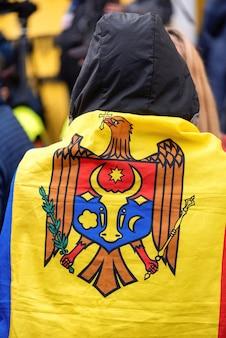 Man in nationale vlag en mensen die protesteren voor vervroegde verkiezingen voor het gebouw van het constitutionele hof
