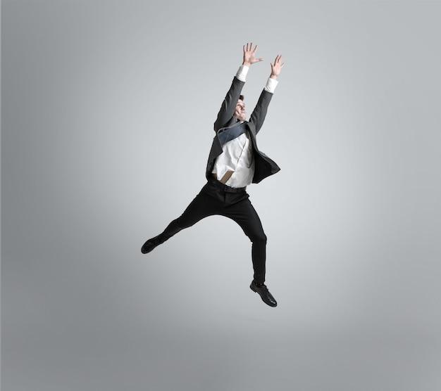 Man in office kleding traines in voetbal of voetbal als doelman op grijze achtergrond.