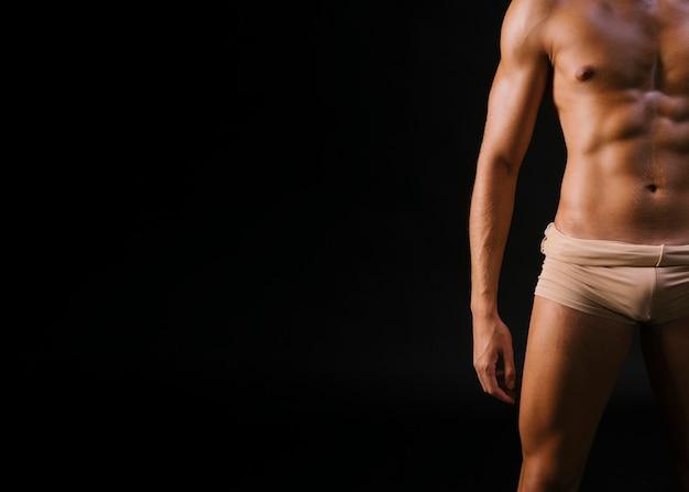 Man in ondergoed tegen zwarte achtergrond