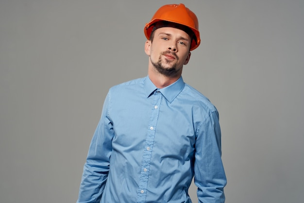 Man in oranje helm blauwdrukken bouwer beroepsberoep