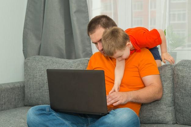Man in oranje shirt probeert te werken op laptop terwijl zijn zoon hem stoort. thuiskantoor werken en blijven thuis conceptie