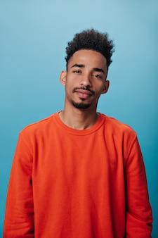 Man in oranje sweatshirt op zoek naar camera op blauwe muur
