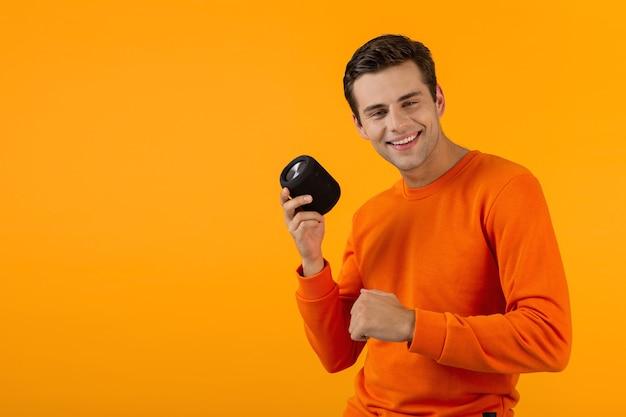 Man in oranje trui met draadloze luidspreker die gelukkig naar muziek luistert en plezier heeft geïsoleerd op geel