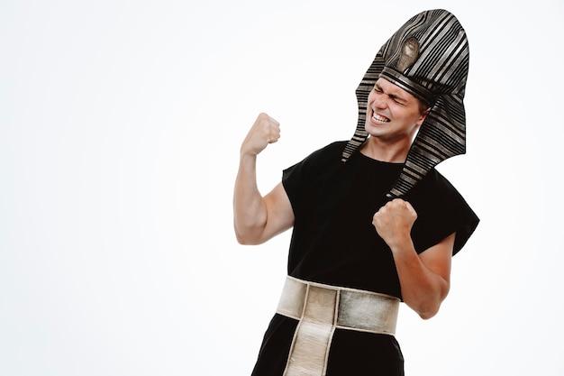 Man in oud egyptisch kostuum, blij en opgewonden, gebalde vuisten die zich verheugen over zijn succes op wit