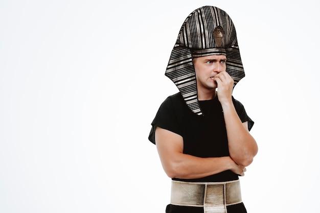 Man in oud egyptisch kostuum die gestrest en nerveus nagels bijt op wit Gratis Foto
