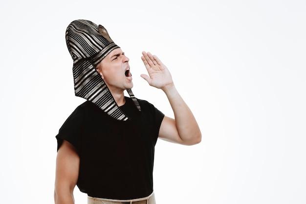 Man in oud egyptisch kostuum die luid schreeuwt of iemand belt met de hand op de mond op wit