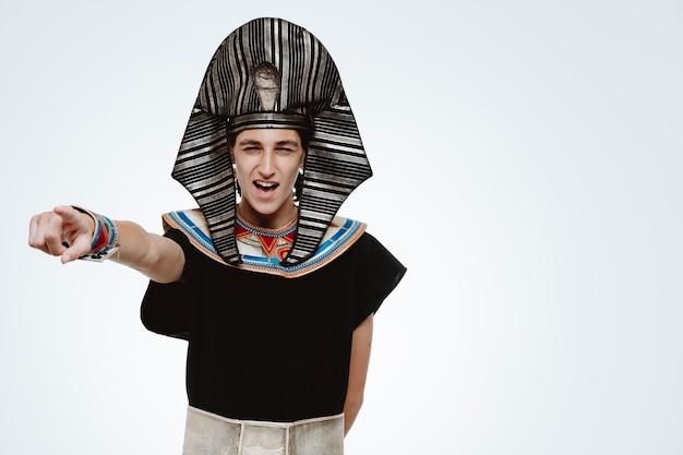 Man in oud egyptisch kostuum glimlachend wijzend met wijsvinger naar de zijkant op wit