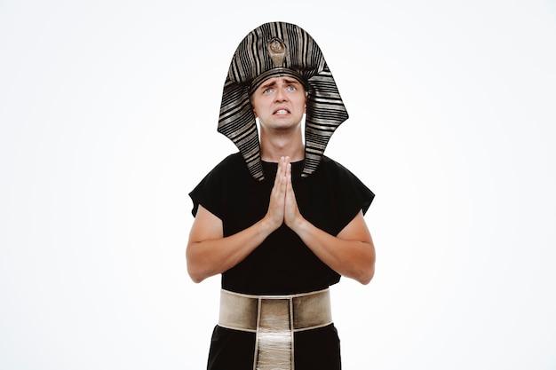 Man in oud egyptisch kostuum kijkt op met hoopsuitdrukking die handpalmen bij elkaar houdt alsof hij op wit bidt