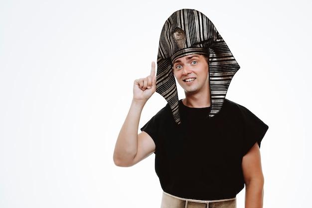 Man in oud egyptisch kostuum met glimlach op slim gezicht wijzend met wijsvinger omhoog met nieuw idee op wit