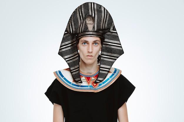 Man in oud egyptisch kostuum met serieuze zelfverzekerde uitdrukking op wit