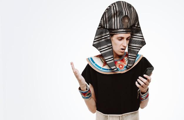 Man in oud egyptisch kostuum met smartphone die ernaar kijkt verward arm opheffen