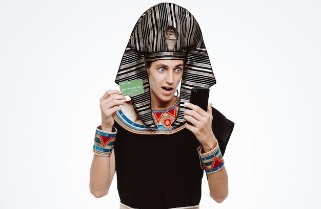 Man in oud egyptisch kostuum met smartphone en creditcard die verbaasd en verrast is op wit