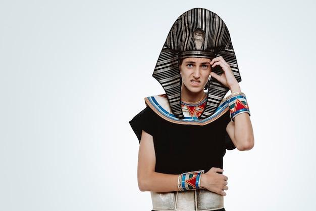 Man in oud egyptisch kostuum verward en bezorgd hand op zijn hoofd houdend voor fout op wit