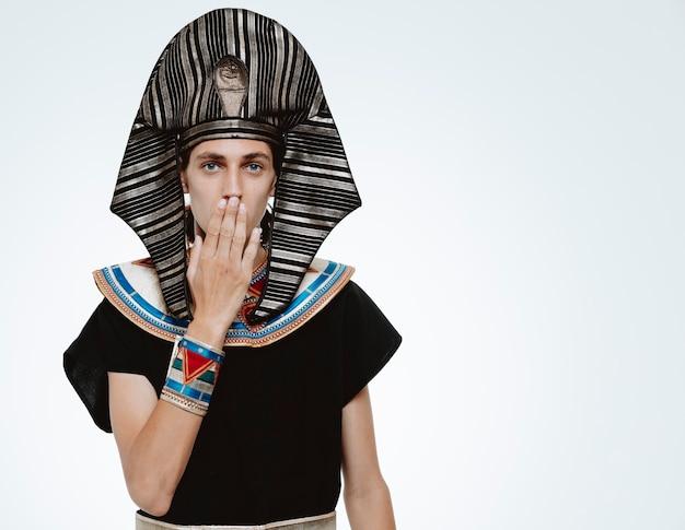 Man in oud egyptisch kostuum wordt geschokt door zijn mond met de hand op wit