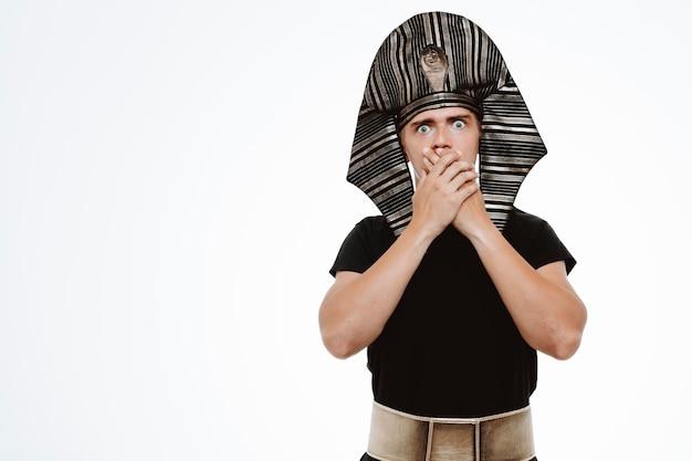 Man in oud egyptisch kostuum wordt geschokt door zijn mond met handen op wit