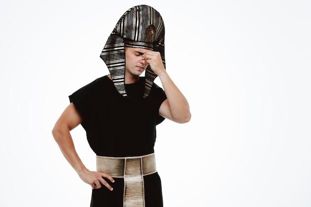 Man in oud egyptisch kostuum ziet er moe en verveeld uit en raakt zijn neus tussen de ogen op wit aan