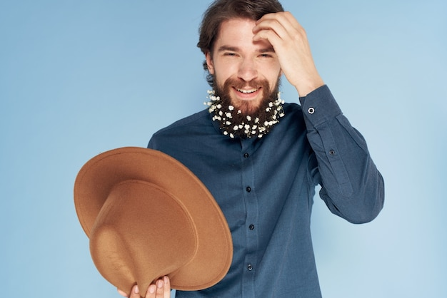 Man in overhemd bloemen in baard hoed emoties elegante stijl blauwe muur.