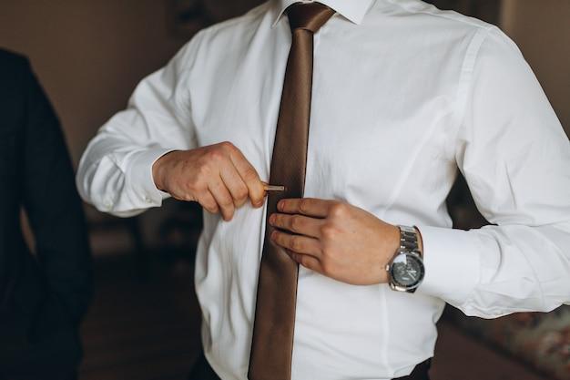 Man in overhemd verkleden en stropdas aanpassen