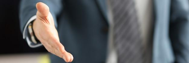 Man in pak die zijn hand geeft voor handdruk close-up zakelijke deals concept