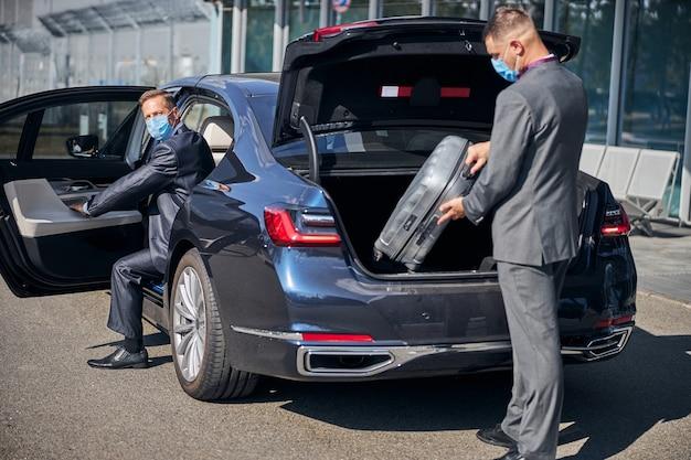 Man in pak en masker is bagage in kofferbak aan het inpakken terwijl elegante baas na aankomst in de auto zit
