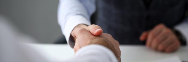 Man in pak en stropdas geven hand als hallo in kantoor