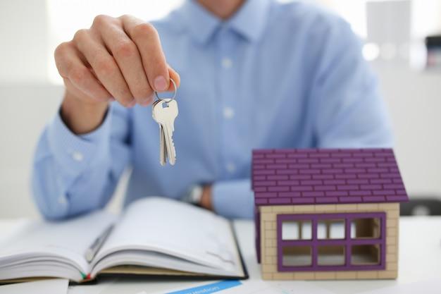 Man in pak en stropdas houden in de hand zilveren sleutel geven