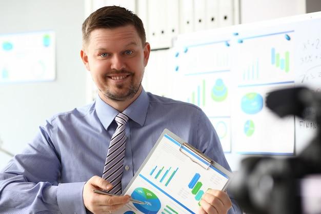 Man in pak en stropdas tonen statistieken grafiekblok