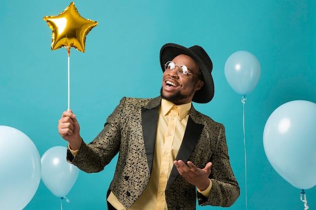Man in pak en zonnebril op feestje met ballon