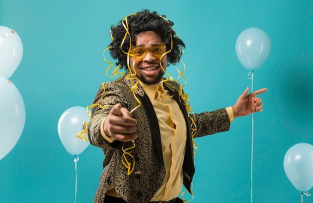 Man in pak en zonnebril op feestje met ballonnen wijzen