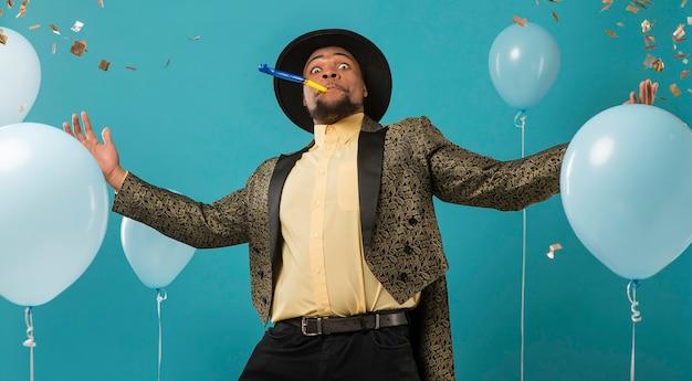 Man in pak en zonnebril op feestje met ballonnen