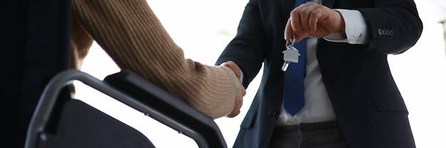 Man in pak geeft huissleutels door aan gehandicapte persoon