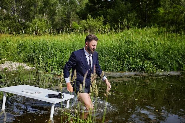 Man in pak, maar zonder broek, verlaat de werkplek in het rivierecosysteem in het wild.