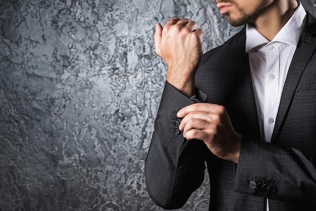 Man in pak manchet van mouw dichtknopen