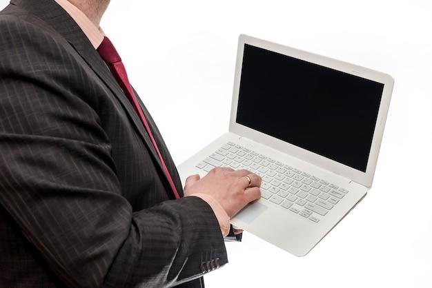 Man in pak met laptop op witte muur