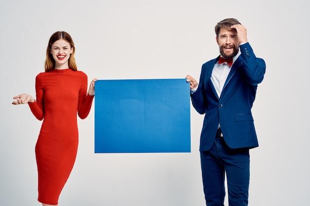 Man in pak naast vrouw in rode jurk blauwe mockup presentatie reclameposter