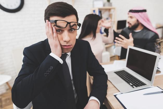 Man in pak op kantoor met arabische man en vrouw.
