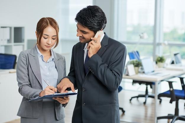 Man in pak praten over telefoon en vrouw maken van aantekeningen