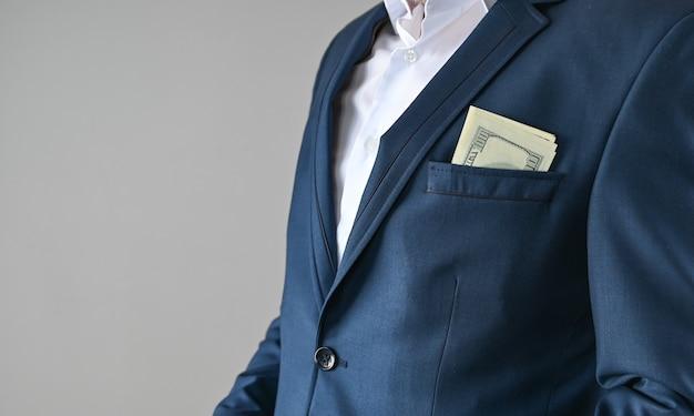 Man in pak stopt geld in zijn zak, corruptieconcept