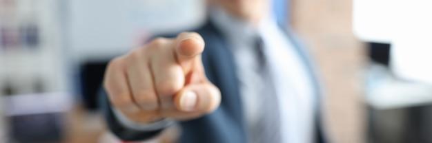 Man in pak wijst met zijn vinger voor hem close-up werkgelegenheid in zakelijke sfeer