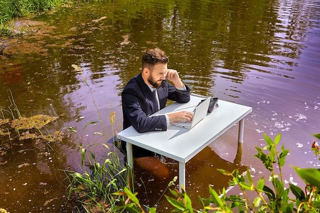 Man in pak zit aan bureau en praat over vaste telefoon, laptop scherm kijken, zakenman werkplek is in de natuur, op rivieroever.