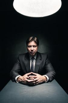 Man in pak zit in een donkere kamer die alleen wordt verlicht door licht van een lamp en in de camera kijkt
