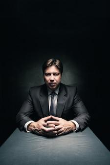 Man in pak zit in een donkere kamer die alleen wordt verlicht door wat licht en in de camera kijkt