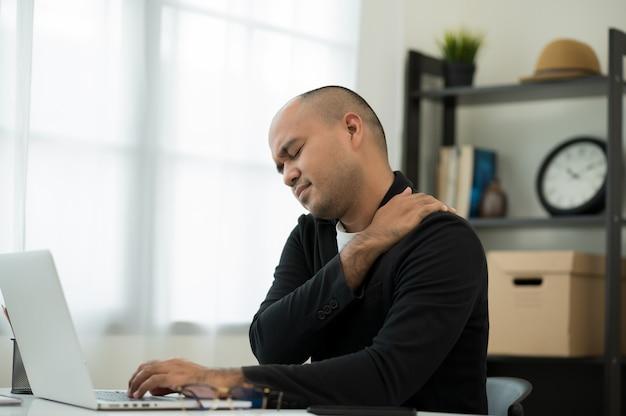 Man in pak zitten in huis werken met laptop hij heeft nekpijn in de schouder
